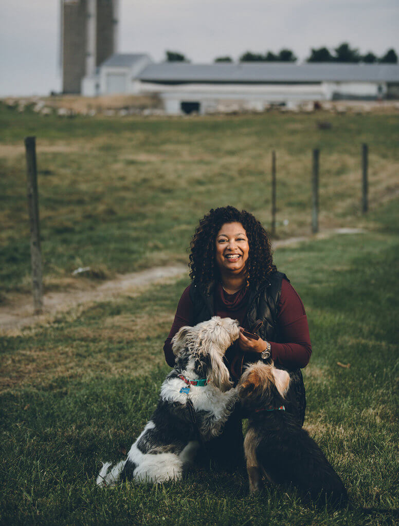 Candace is pictured kneeling in the grass with two dogs in front of her with a farm in the background