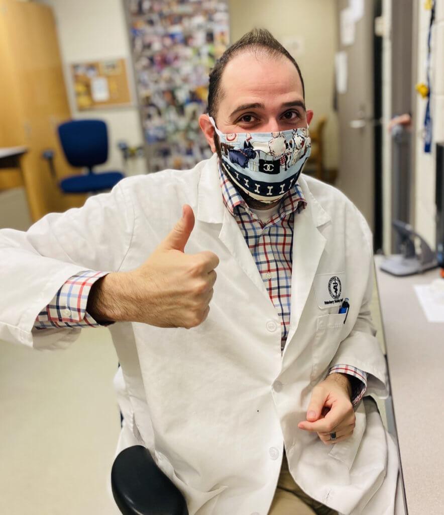 Dr. Fulkerson wears a white coat and face mask as he sits giving a thumbs up