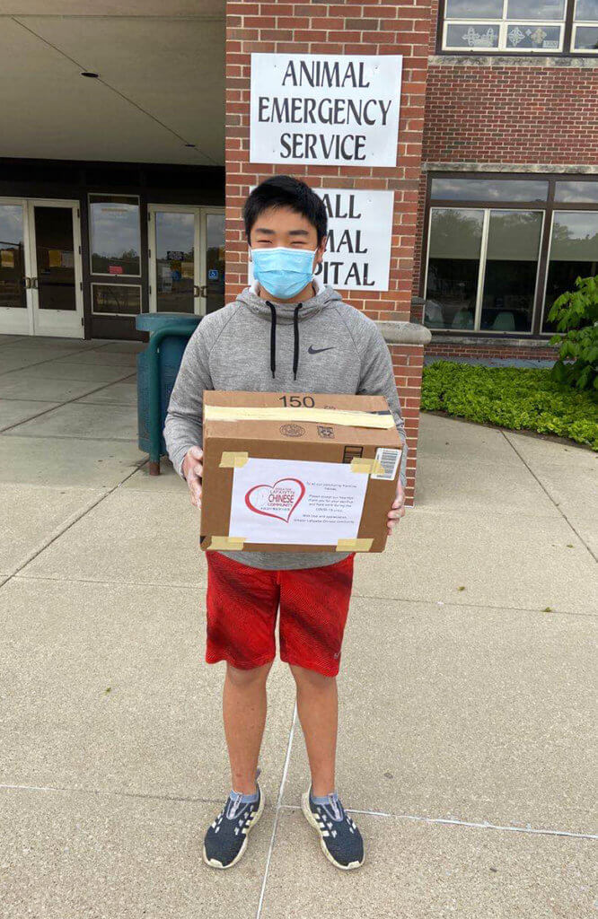 A boy wearing a facemask holds a box in front of the Small Animal Hospital