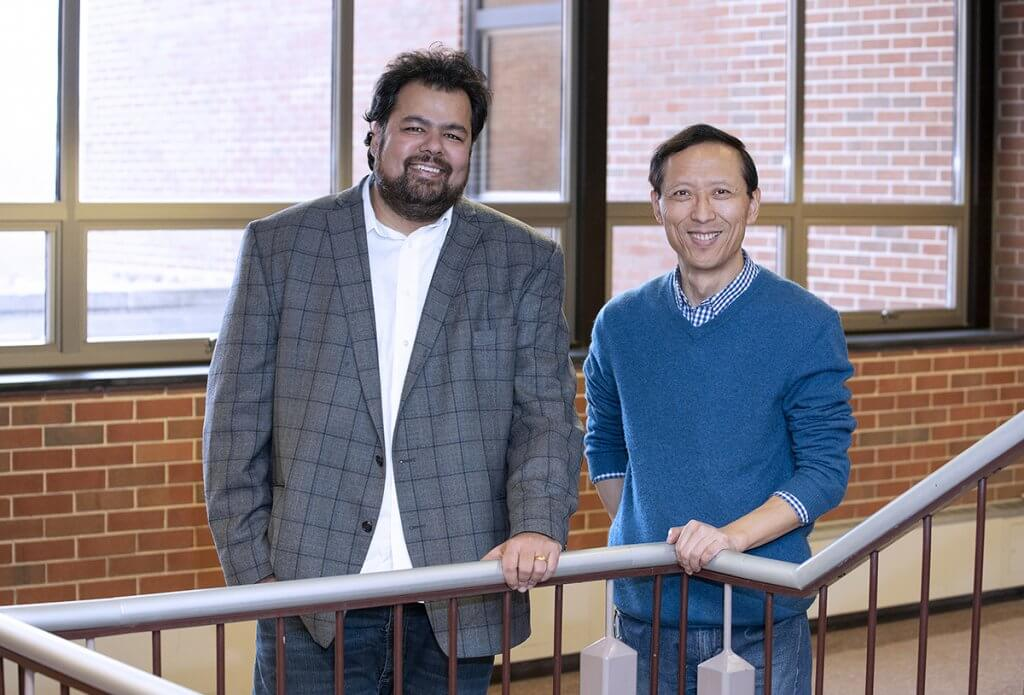 Dr. Chopra and Dr. Shi stand together along a staircase in Lynn Hall