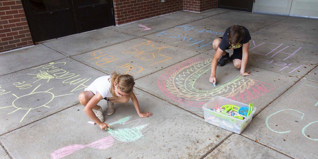 children decorate with sidewalk chalf