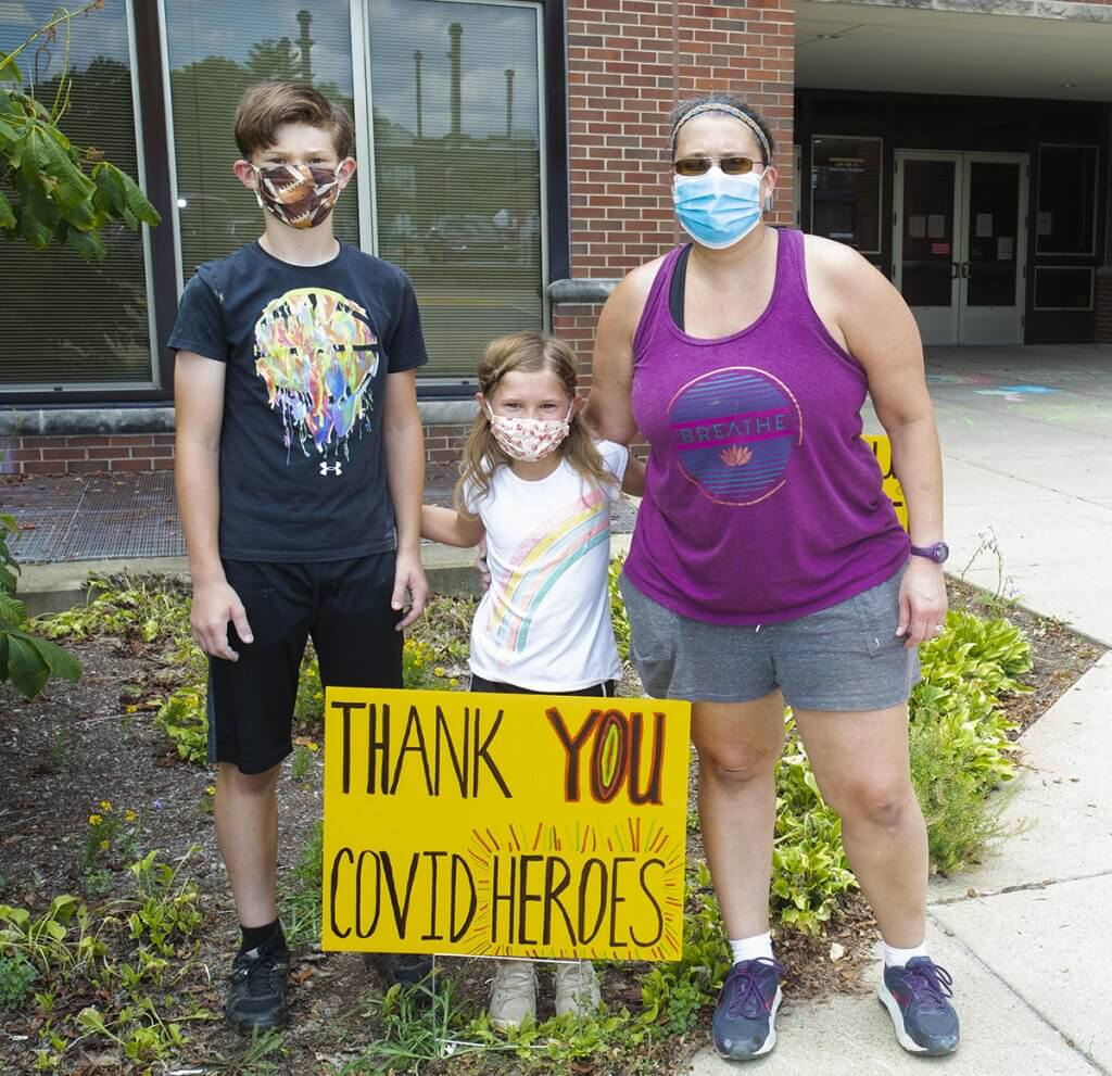 Kaden, Sophia and Lisa stand behind the yard sign outside