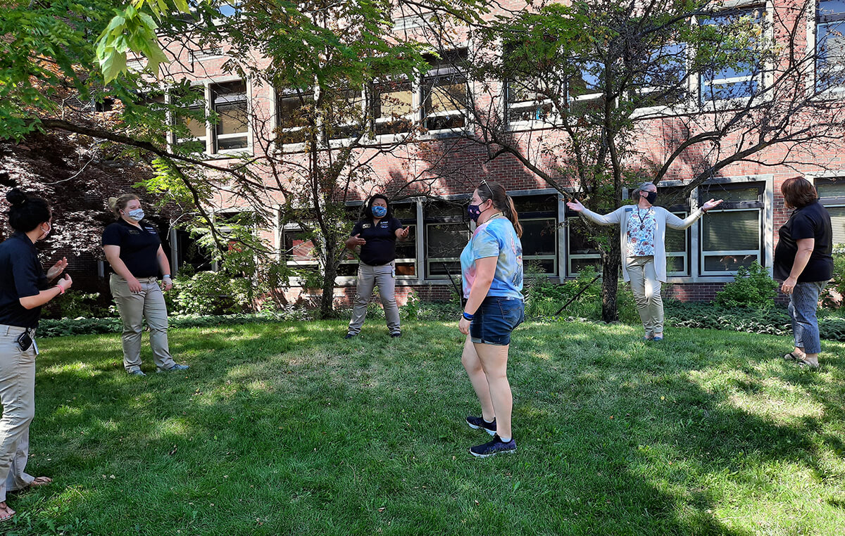 Students and staff stand socially distanced in the grass