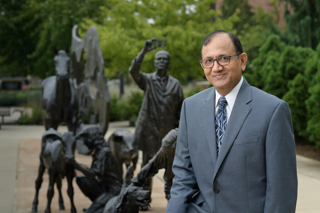 Suresh Mittal pictured standing in front of the Continuum sculpture outside Lynn Hall