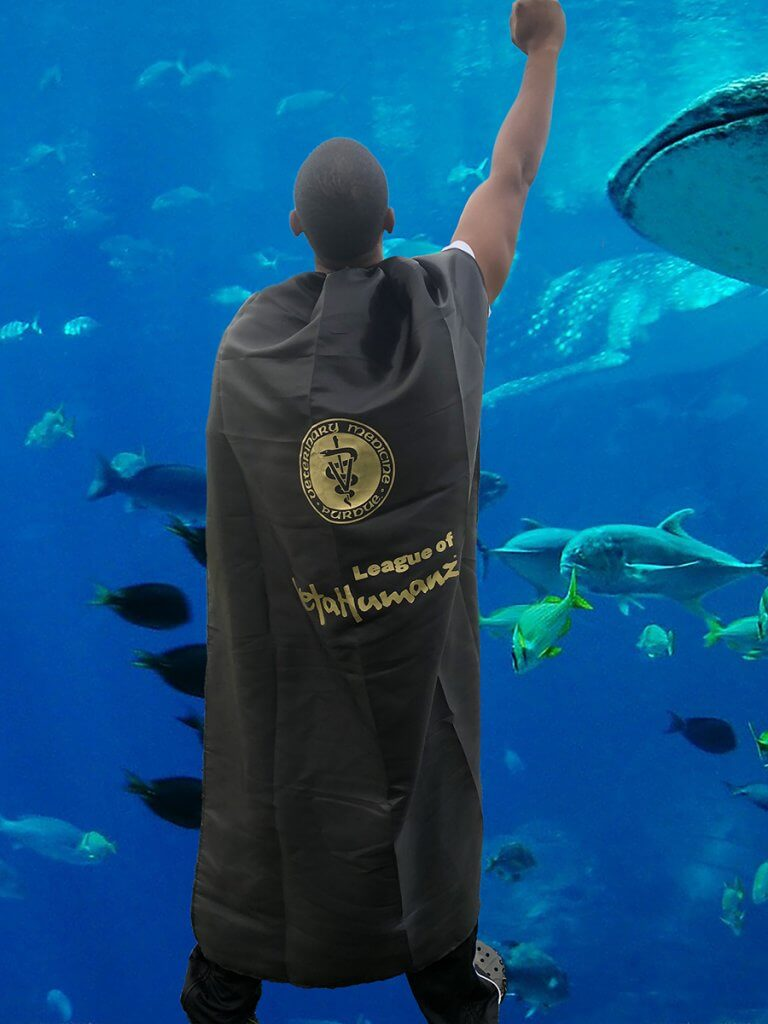 Dr. Hines raises his fist in the air as he wears a superhero cape in front of a aquarium full of fish and sharks