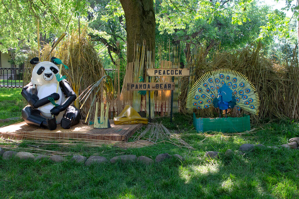 A panda and peacock are pictured in a scene all created from recycled materials