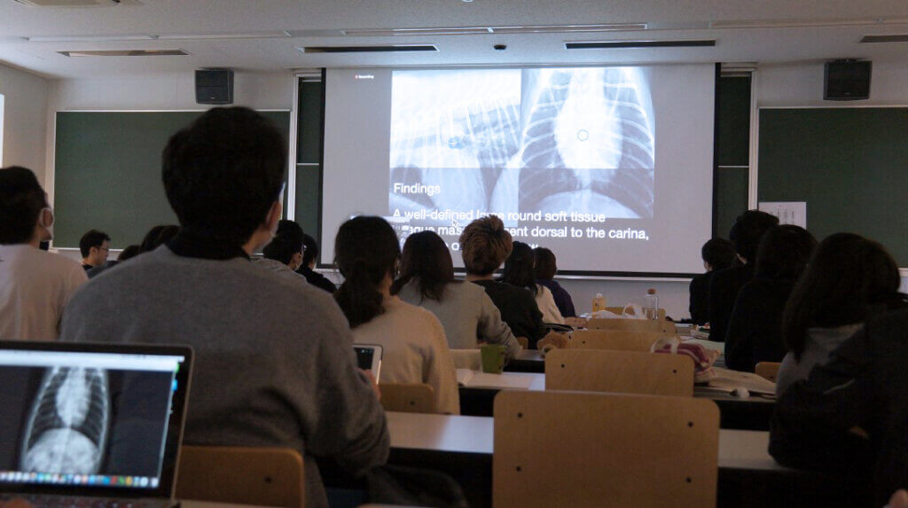 View from the back of a classroom in Japan as students watch the presentation projected on a screen at the front of the class