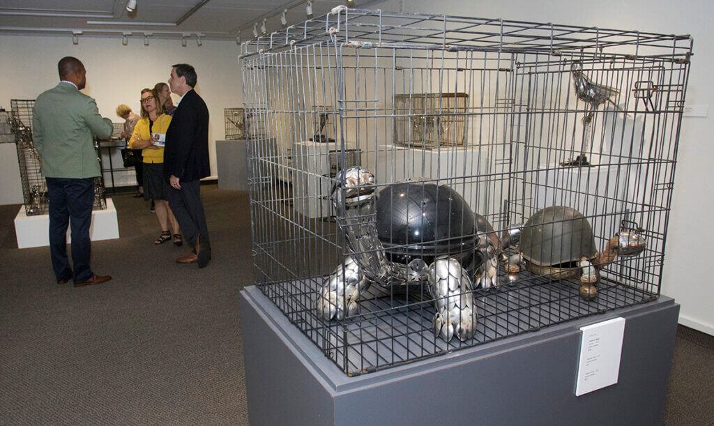 Metal sculpture of turtles in a cage is displayed in the museum with gallery attendees standing in the background