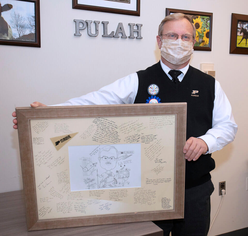 Pat holds up the framed caricature. He's wearing celebratory retirement pins on his vest.
