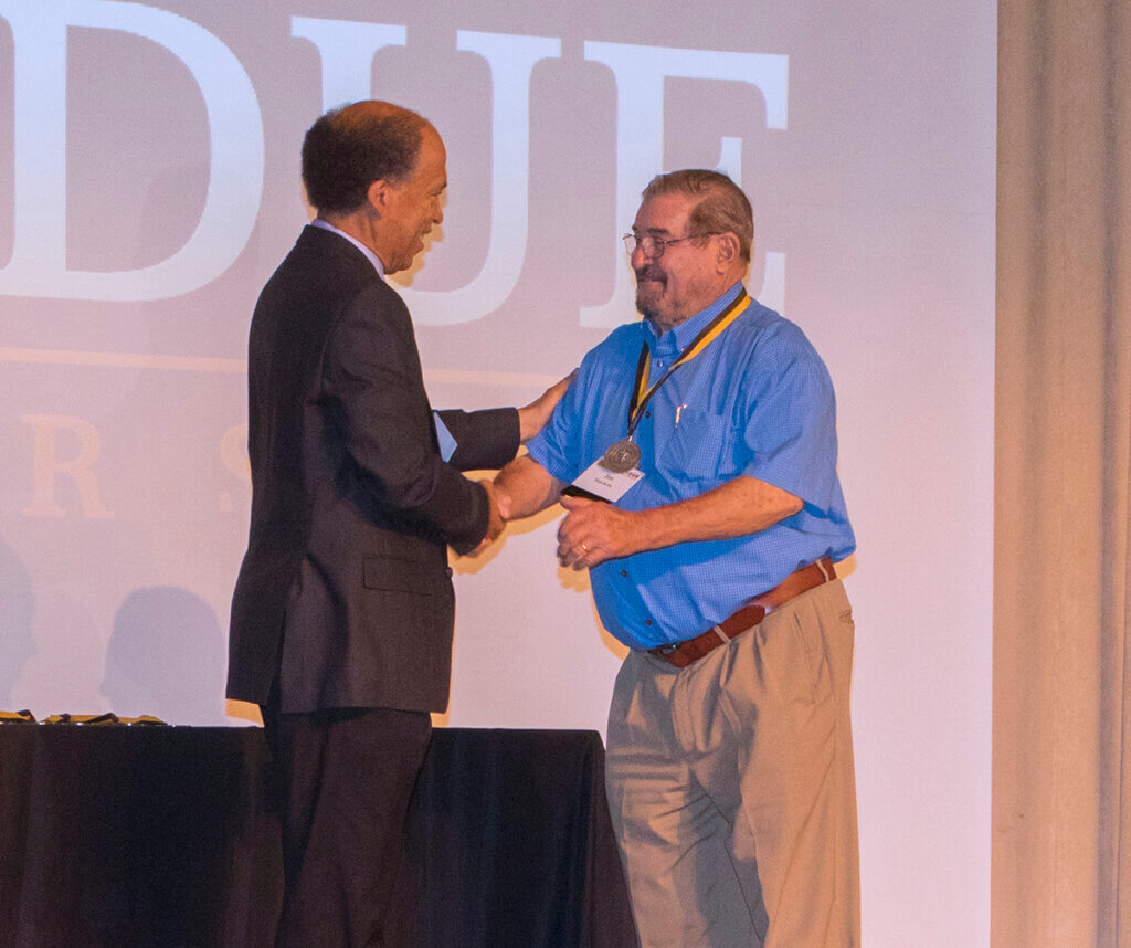 Dean Reed shakes Dr. Matchette's hand in congratulations