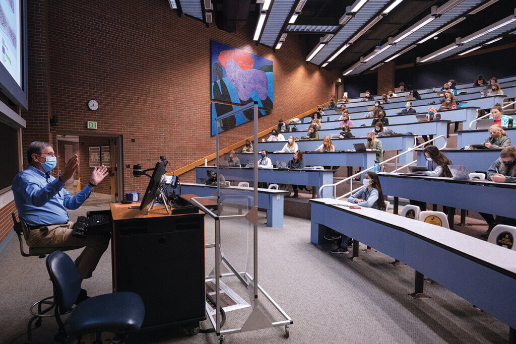 Dr. Turek sits behind a plexiglass shield as students sit distanced in the lecture hall