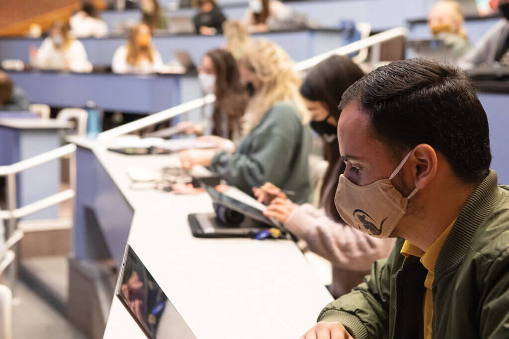 A student wears a face mask while looking at his laptop with fellow classmates seated around him in the background