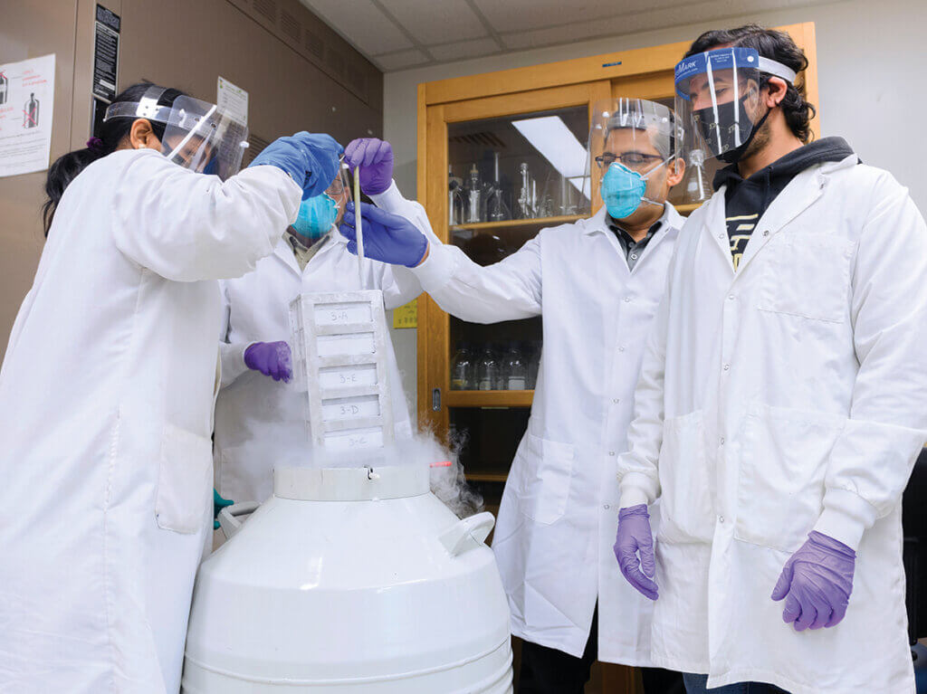 Dr. Mittal and his team work in his lab wearing protective gear