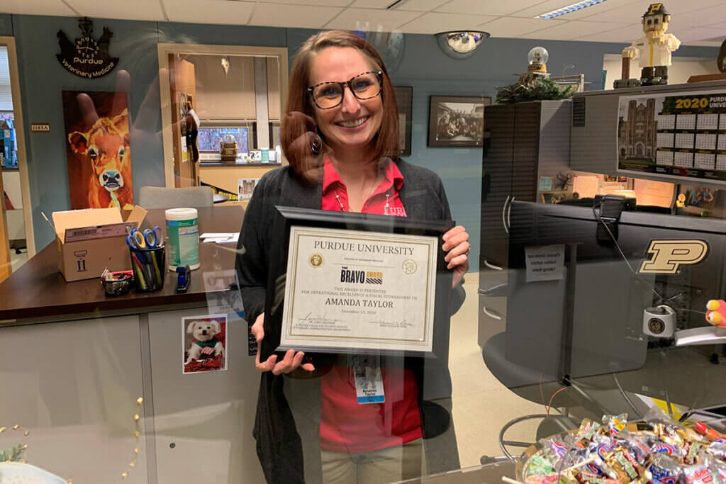 Amanda holds up her Bravo Award certificate behind her desk in Student Services