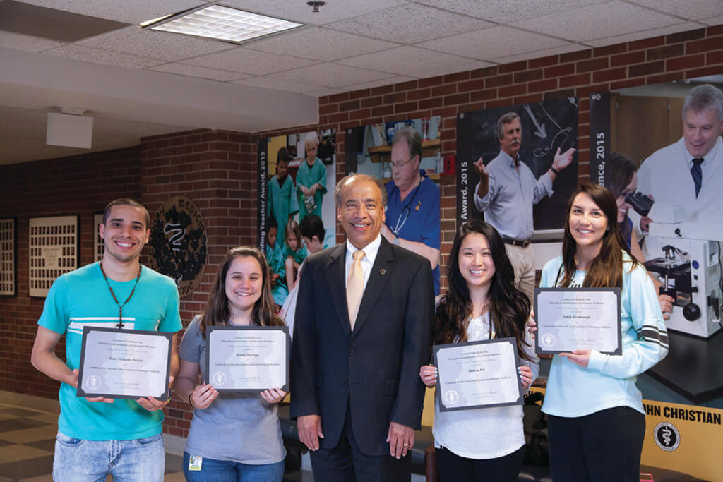 Dean Reed stands alongside students smiling and holding up their certificate of completion