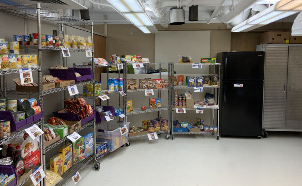shelves line the walls with organized groups of food and displayed next to a refrigerator and freezer
