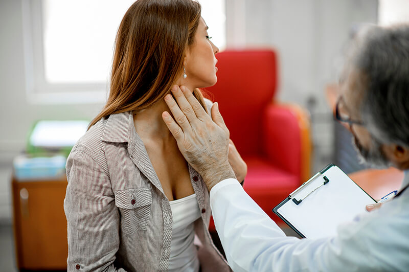 a doctor examines a woman's throat