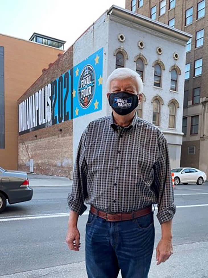 Dr. Borst stands in front of a Final Four basketball mural on a building in downtown Indianapolis, while wearing a March Madness face mask