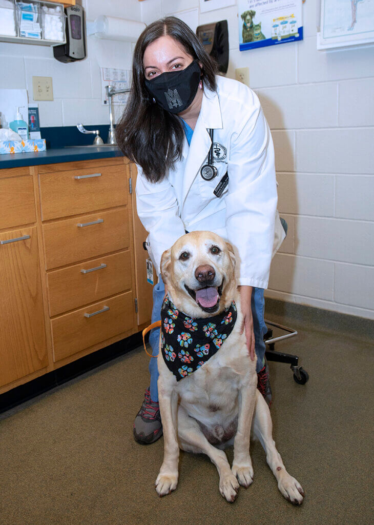 Cooper sits in an exam room along with Dr. Sarah Malek who sits behind him touching his shoulder.