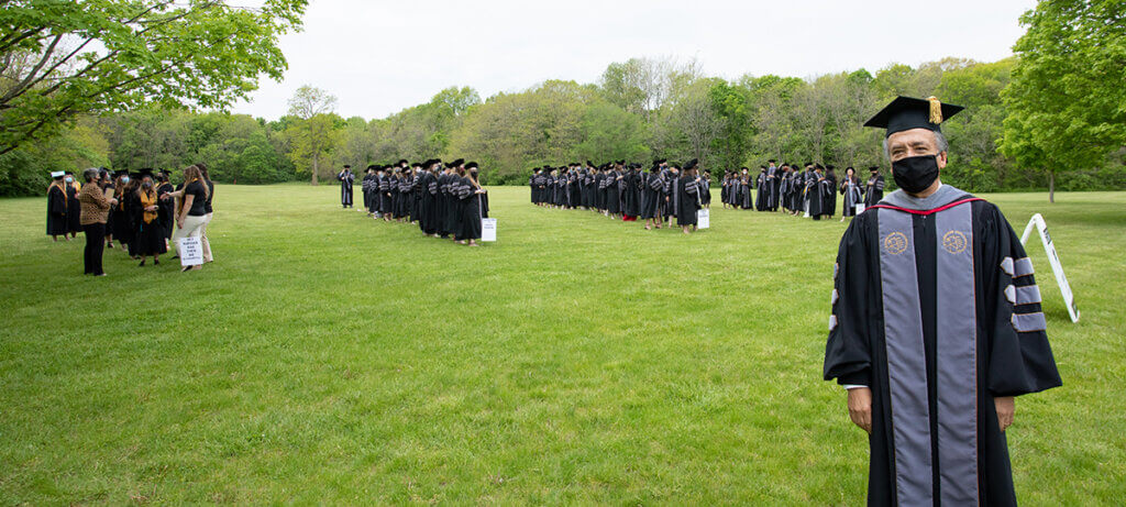 Dean Reed stands in ceremonial garb wearing a face mask as graduates are lined up in the background on the grassy lawn
