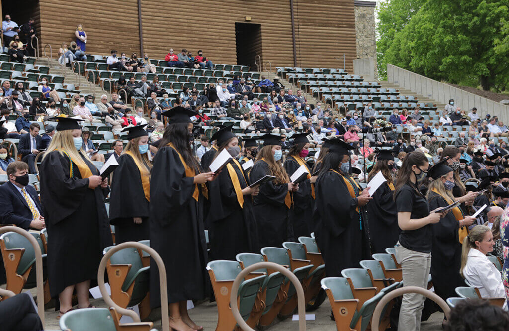 Veterinary medicine graduates stand in front of their seats and read the oath from the event program