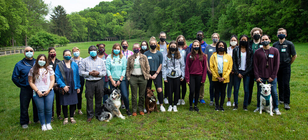 veterinary scholars and some faculty members along with some pets gather for a group photo while wearing masks outside against a lush green backdrop of the park