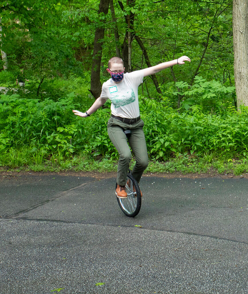 Keely balances on the unicycle with her arms stretched out