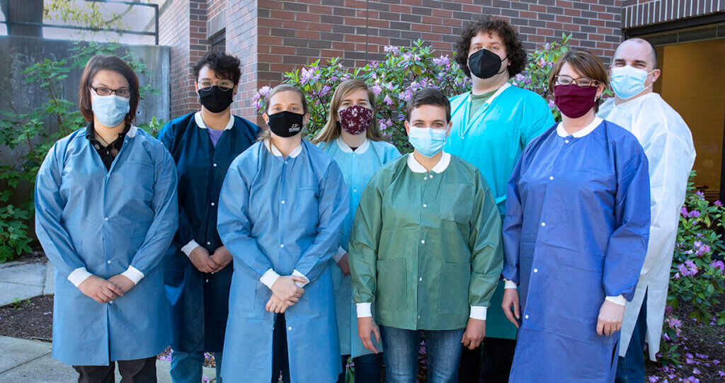 The Molecular Laboratory team gathered together for a group photo in the courtyard donning lab coats and face masks