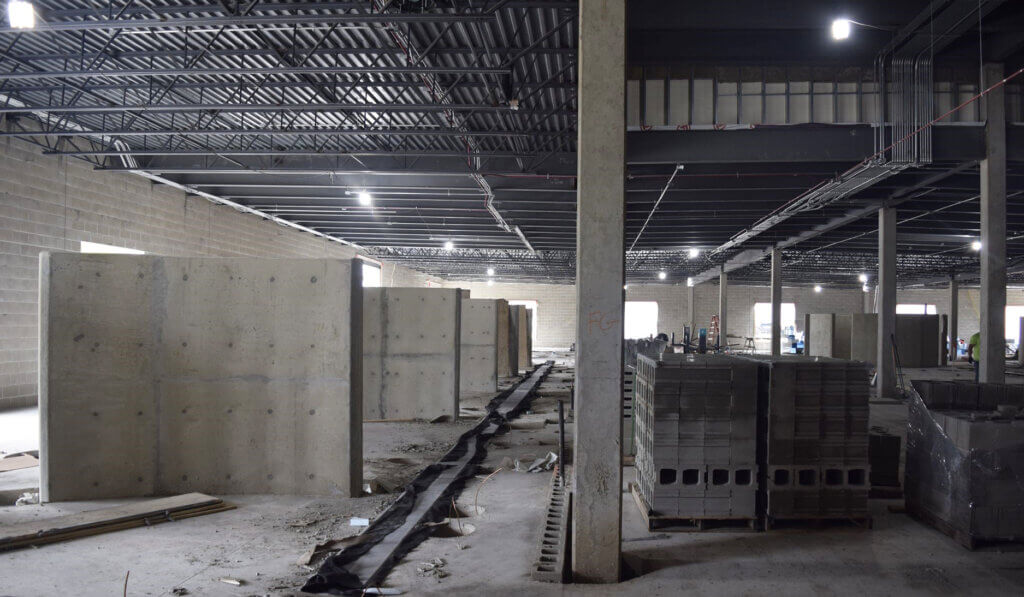 Freestanding walls are spaced out to the left of the space with pallets of cinder blocks lined up on the right
