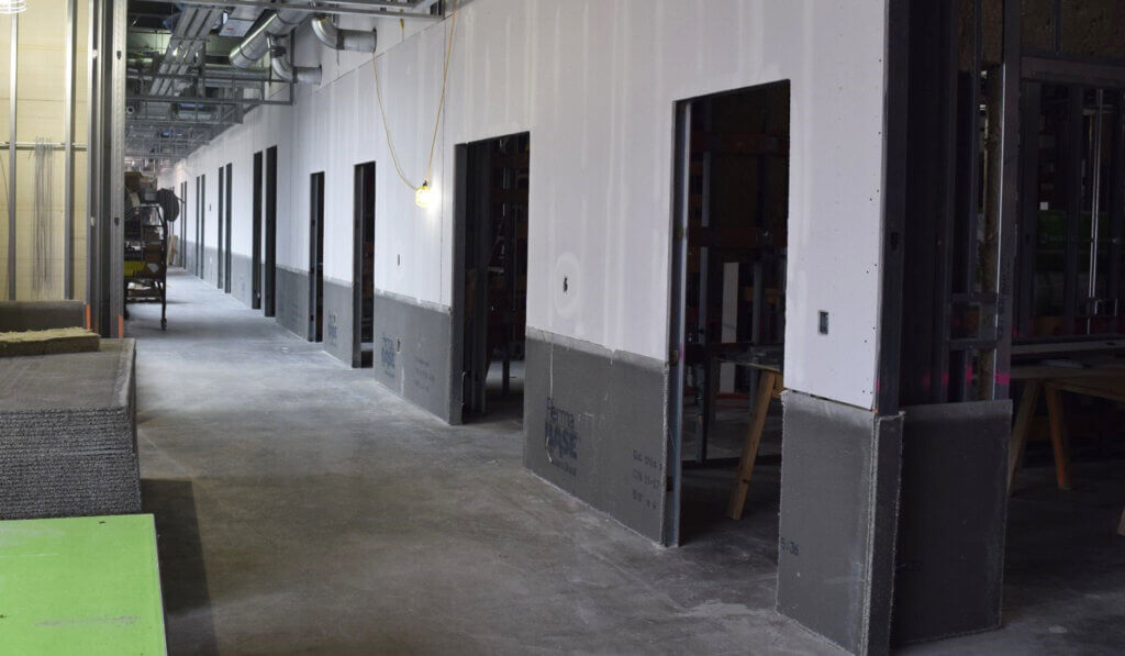 A hallway of doorways cut into the drywall outline future exam rooms