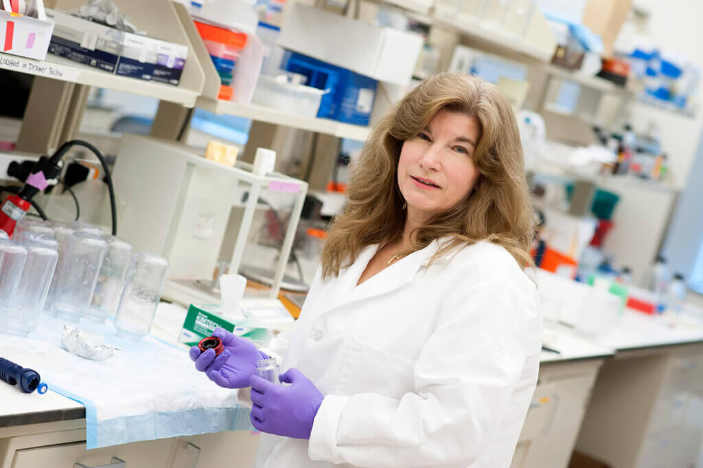 Dr. Harbin pictured in her lab holding a device