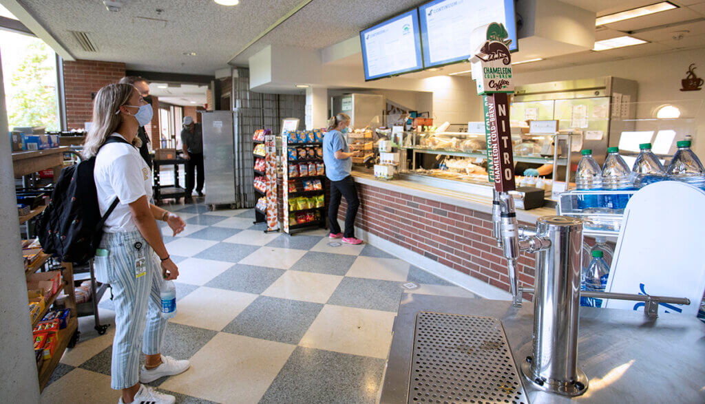 the cold brew tap is pictured in the cafe with nearby students standing by looking at the menu screens