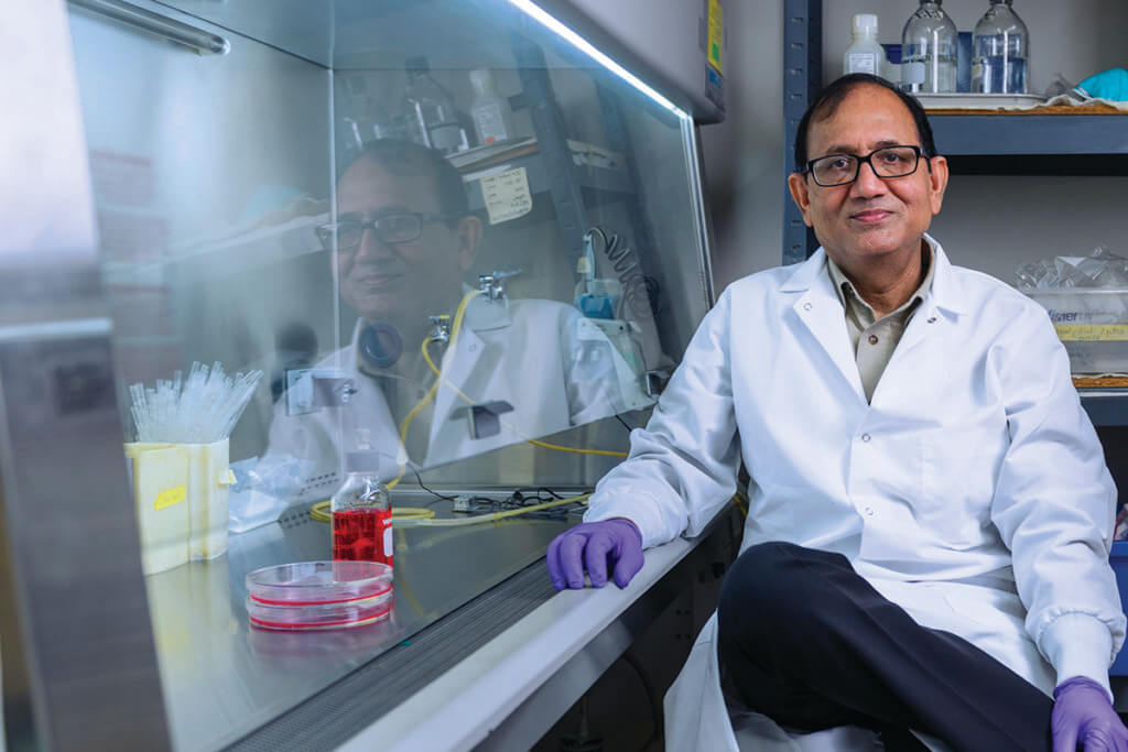 Dr. Mittal sits in his lab wearing a white coat and purple gloves smiling