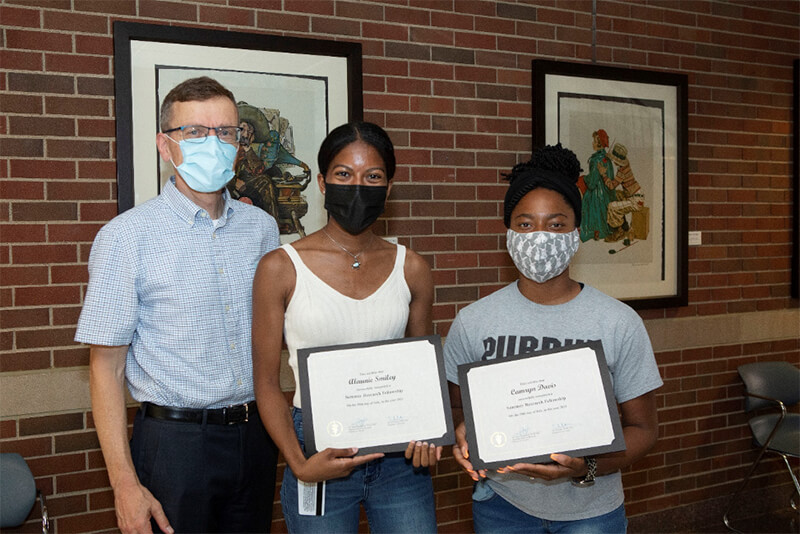 Associate Dean HoegenEsch with students Smiley and Davis holding their diplomas
