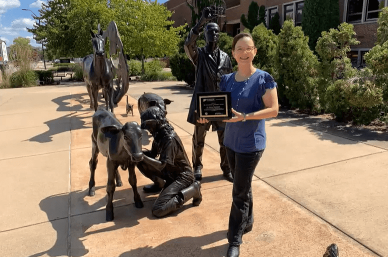 Marxa is pictured with her award plaque standing next to the Continuum sculpture in front of Lynn Hall