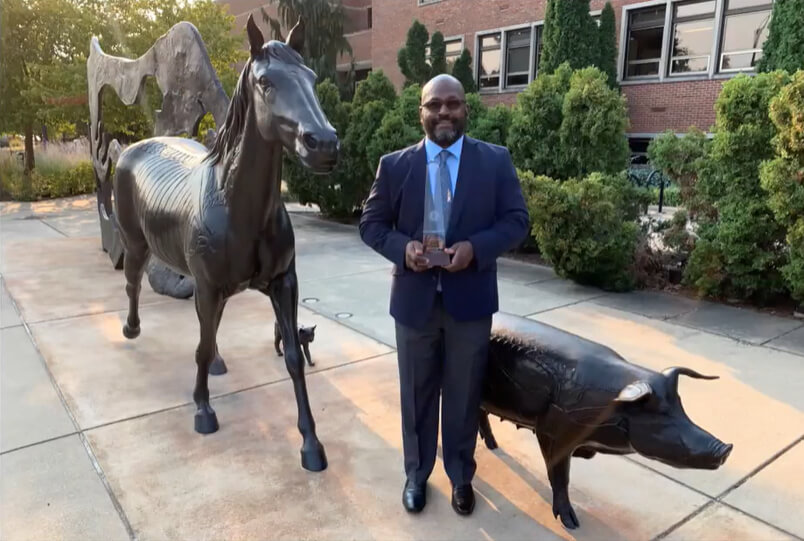 Dr. Ragland stands alongside the swine sculpture in the Continuum sculpture installation in front of Lynn Hall