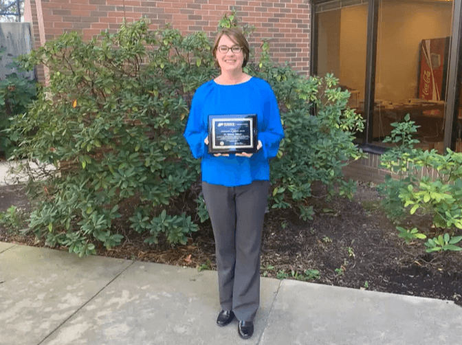 Rebecca smiles while holding her award plaque outside the diagnostic lab