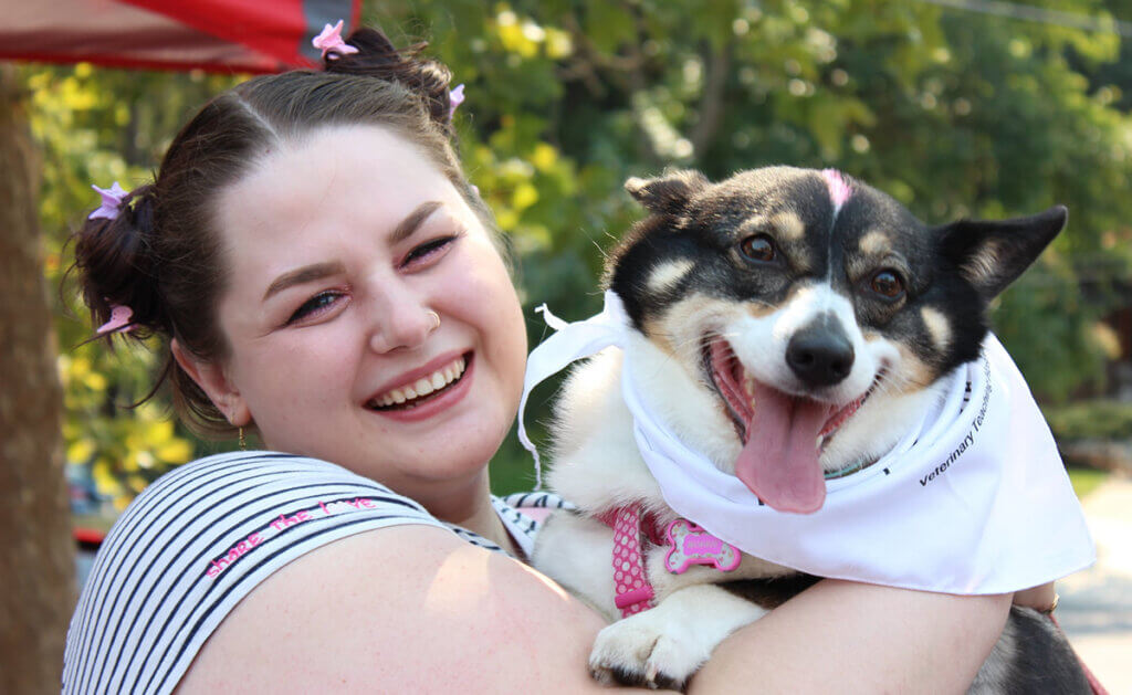 A woman smiles holding her small smiling black and white dog sporting a PVM bandana