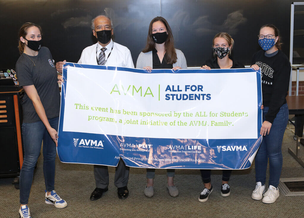 Dean Reed and students stand behind a large banner sign recognizing the AVMA All for Students program