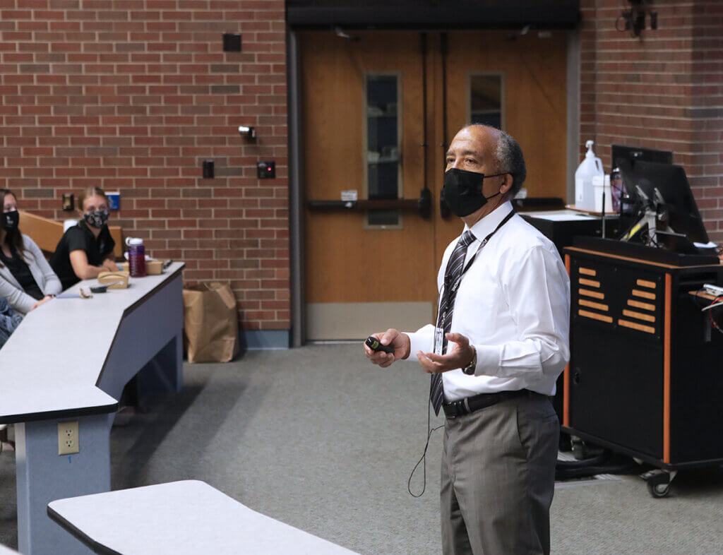 Dean Reed speaks to students from the front of the classroom wearing a mask and holding a presentation pointer