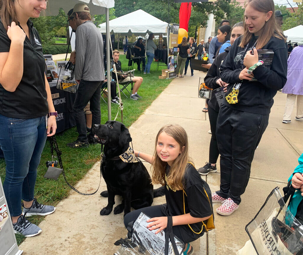 Bethany kneels down to pet Finn as she looks toward the camera smiling