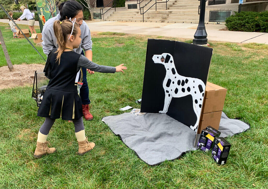 """A little girl wearing a Purdue cheerleading outfit in black and gold tosses a """"tick"""" onto the spotted dog backdrop as a PVM volunteer stands by to assist"""
