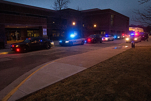 Police from multiple departments escort a Lake County Sheriff's Department squad car as it arrives at Lynn Hall Wednesday evening, January 18, with Blade, a police K-9 that was injured in a shooting in Gary, Ind.