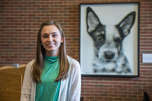 Katie Sands, of the DVM Class of 2018, poses with her string art portrait, 'Rue.' The portrait can be found on the north wall of the Quiet Study section of the Veterinary Medical Library.