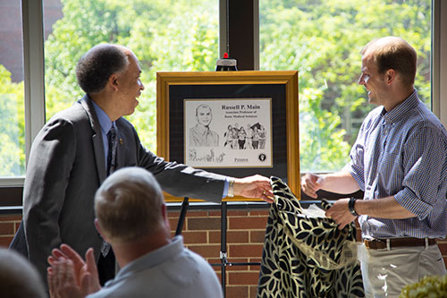 Dean Willie Reed and Dr. Russell Main unveil the caricature created by Professor of Medical Illustration David Williams commemorating Dr. Main's promotion to associate professor of basic medical sciences at the annual PVM Faculty Promotions Reception in the Continuum Café Tuesday, May 16.