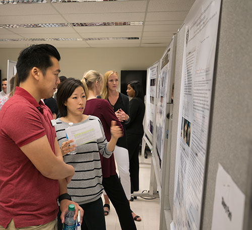 Shery Park, of the DVM Class of 2020, discusses her research findings along with fellow PVM Summer Research Program participants at the annual poster presentation in Lynn Hall.