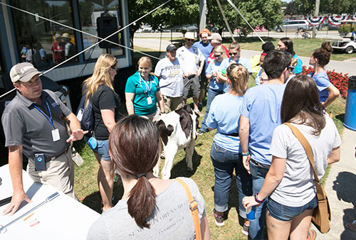 Dr. Jonathan Townsend (lower-left corner), stands outside the veterinary surgery unit at the Indiana State Fair, talking to the general public after an educational lecture on the role of dairy cows in Indiana. In addition to participating in educational talks like these, Dr. Townsend helps coordinate veterinary medical services for all the exhibition animals at the fair.