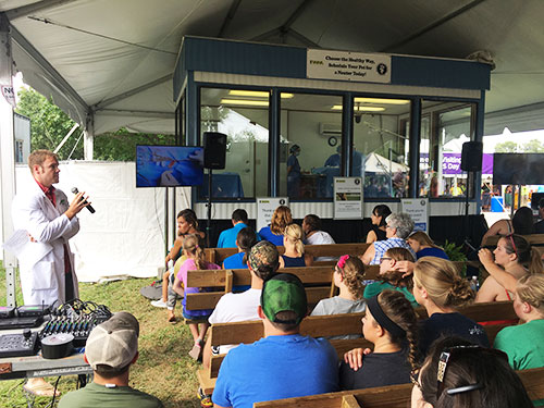 Dr. Eric Hans (PU DVM 2011) narrates as Purdue Veterinary Medicine faculty and staff perform a live neuter surgery in the sterile surgery demonstration suite co-sponsored by the College and the Indiana Veterinary Medical Association at the Indiana State Fair.