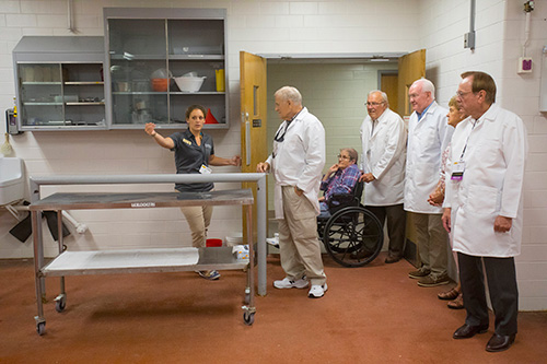 Alexis Zobel of the DVM Class of 2018 leads a tour group from the Golden Anniversary Class of 1967 through the Large Animal Hospital.