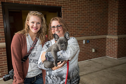 Puppy Cuddles event coordinator Andi Waibel with her friend Paige Kiger, who brought her cuddly French bulldog, Carl, to the United Way fundraising event Wednesday (October 11) at the east entrance to Lynn Hall.
